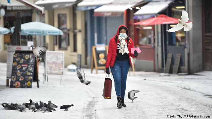 Woman walks along a snow-covered street in Brussels