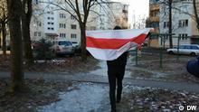 Человек с бело-красно-белым флагом в одном из минских дворов