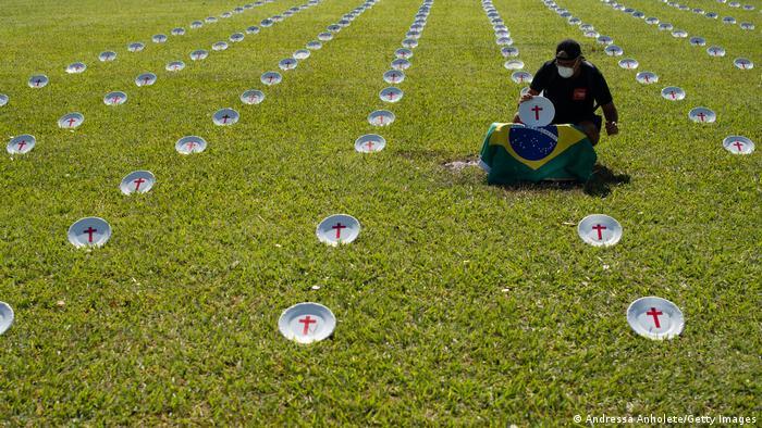 Pratos com cruzes vermelhas estão dispostos em gramado em ato de protesto em Brasília