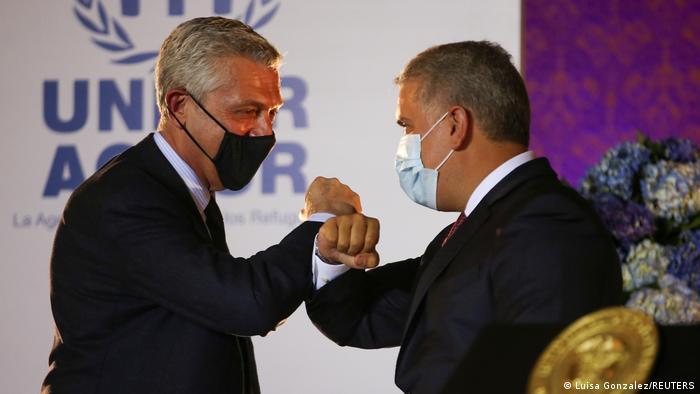 Filippo Grandi (links) und Ivan Duque (rechts), beide mit Mundschutz, stoßen vor einem Loge des UNHC ihre Ellbogen aneinander als Zeichen der gegenseitigen Sympathie in Pandemie-Zeiten