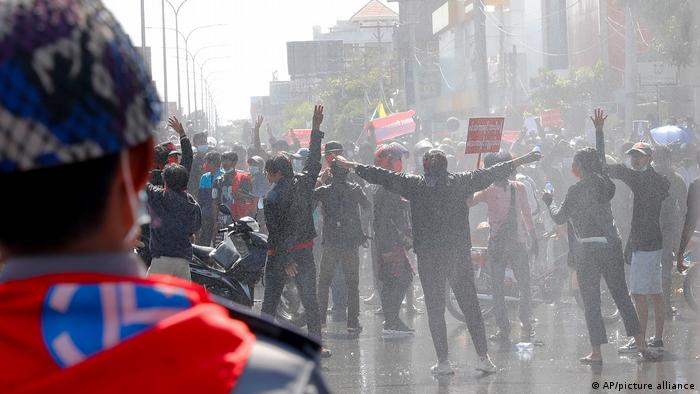 Protesters regroup after police fired warning-shots and use water cannons during a protest in Mandalay