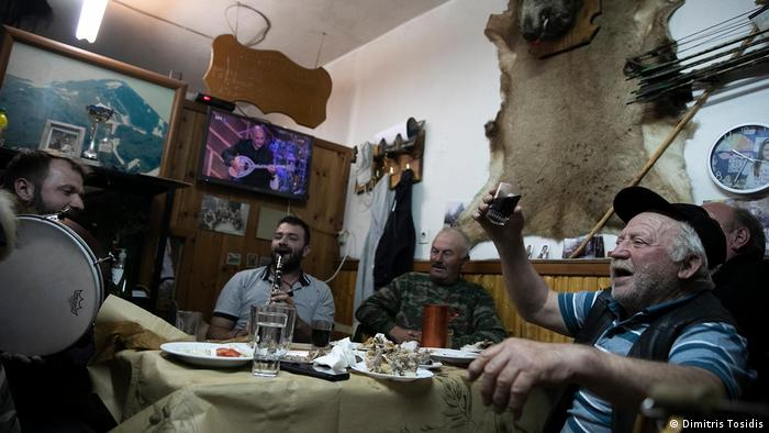 Giorgos Anthoulis celebrates with other locals in a tavern in Greece