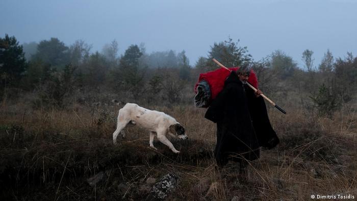 A shepherd walks in the morning fog carrying heavy blankets in Greece