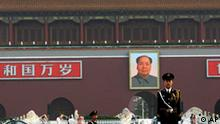 With a backdrop of a portrait of China's late communist leader Mao Zedong, center, a Chinese paramilitary policeman, right, stands still while another yawns while marching, in Tiananmen Square in Beijing, China, Friday, June 4, 2010. Chinese authorities tightened security on the vast square during the anniversary of the deadly 1989 crackdown on pro-democracy protestors, which is marked today. (AP Photo/Muhammed Muheisen)