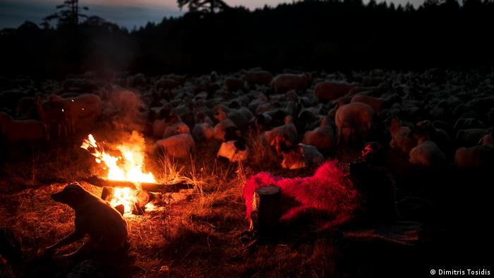 Giannis Saitis gets ready for bed beside a fire in the open