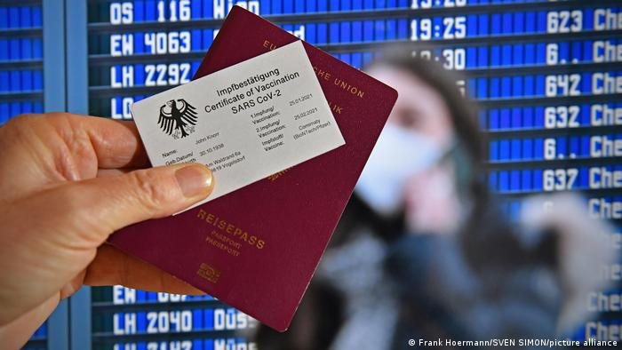 A hand holding a passport and a vaccination certificate - an airport flight departure board in the background