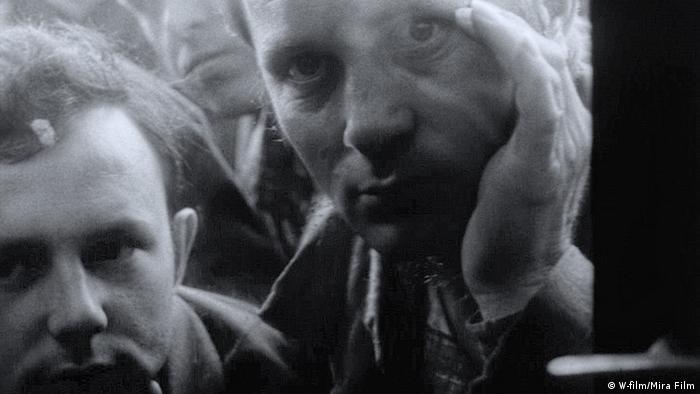 Schwarzweißfilmstill zeigt zwei Männer, die durch eine Scheibe blicken.