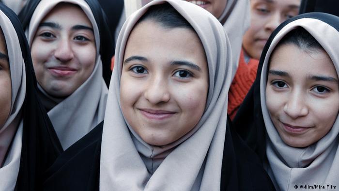 Iranische Mädchen mit Kopftuch lächeln in die Kamera.