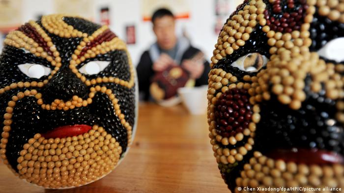 Peking Opera masks made of beans and cereals by Chinese farmer Sun Xiaodong are displayed at home in Zhangjiakou city