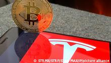 Монета із символом біткоїна на тлі логотипу Tesla