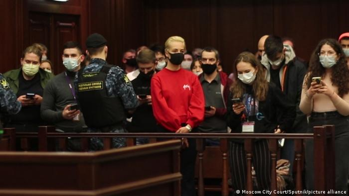 Security guards and other people standing in a courtroom, with Yulia Navalnaya standing in the middle and wearing a red sweater and a black face mask.