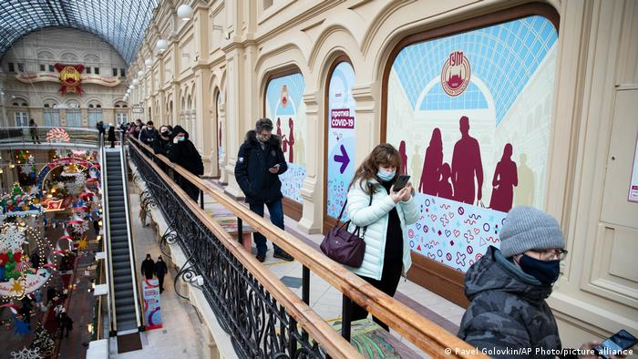 People stand in a queue to get a shot of Russia's Sputnik V coronavirus vaccine in a vaccination center in GUM State Department store in Moscow
