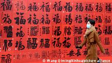 (210210) -- SHAOYANG, Feb. 10, 2021 (Xinhua) -- A woman walks past an exhibition poster of the Chinese character Fu, meaning blessings, for the upcoming Chinese Lunar New Year in Changzhou City, east China's Jiangsu province, Feb. 10, 2021. (Photo by Wang Qiming/Xinhua)