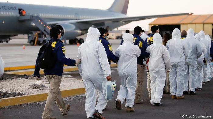 En Chile, la deportación con overoles blancos y custodia policial fue una clara señal de las autoridades del país sudamericano.