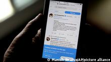 A man reads tweets by Indian celebrities, one of the many backing the Indian government