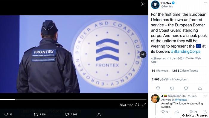 Man seen from back wearing Frontex uniform, standing next to a Frontex logo