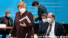 German Chancellor Angela Merkel, front left, walks past Helge Braun, Head of the Chancellery, right, as she arrives for the weekly cabinet meeting in Berlin, Germany, Wednesday, Feb. 10, 2021. (AP Photo/Michael Sohn, pool)