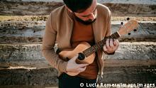Homem de barba tocando ukulele