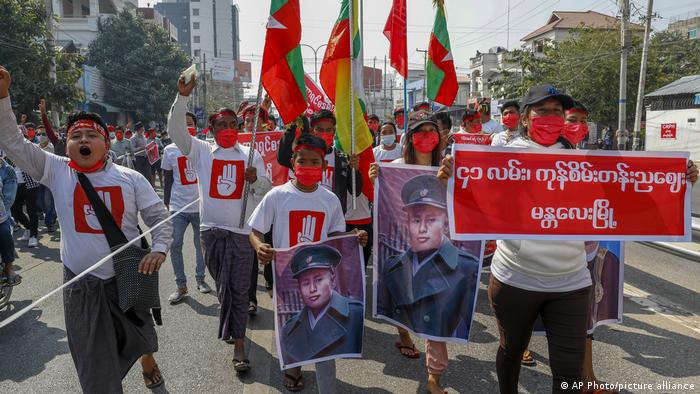 Demonstrators with pictures of Gen. Aung San, father of ousted Myanmar leader Aung San Suu Kyi shout slogans against the military coup during a protest in Mandalay, Myanmar on Thursday, Feb. 11, 2021.