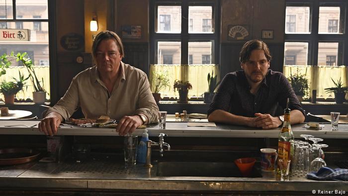 Film still 'Next Door': Actors Peter Kurth and Daniel Brühl sitting at a bar