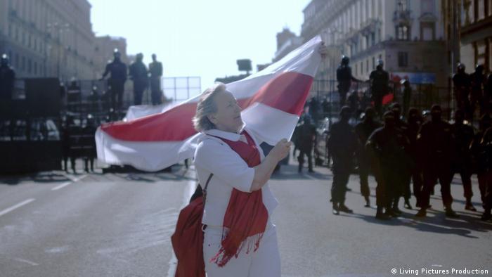 Szenenbild aus Courage: eine Frau schwingt die Fahne von Belarus vor Polizisten
