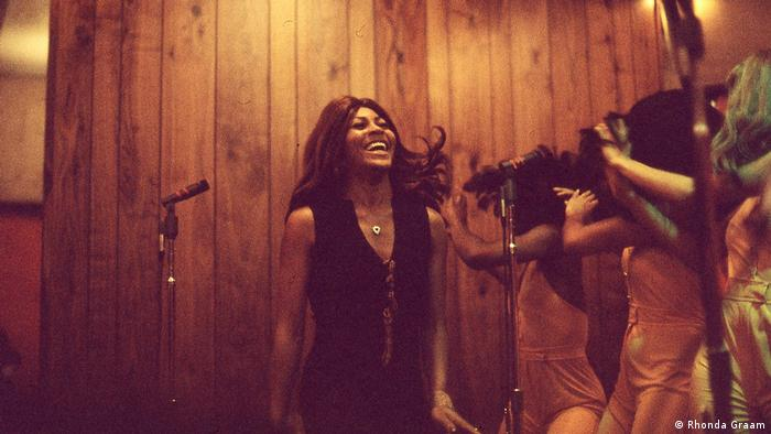 Film still 'Tina': A young Tina Turner smiling in a recording studio with the Ikettes