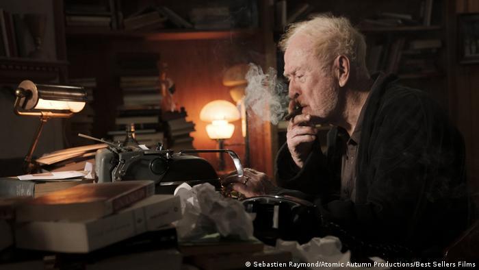 Film still 'Best Sellers', Michael Caine smoking in dark office