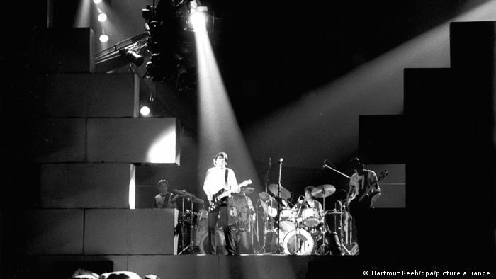 Pink Floyd-Konzert The Wall in Dortmund: Man sieht die Band noch durch die bereits enstehende Mauer hindurch, das Scheinwerferlicht ist auf Waters gerichtet