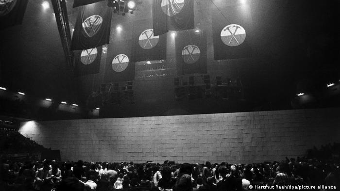 Pink Floyd-Konzert The Wall in Dortmund: Von der Decke hängen Fahnen, vor dem Publikum sieht man eine lange, hohe Mauer