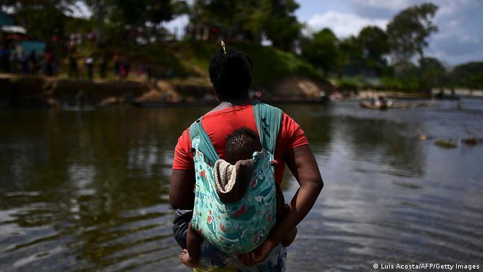 Foto simbólica de una mujer migrante que lleva a un bebé en la zona del Darién
