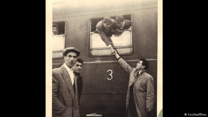 A still from the film shows men next to a train