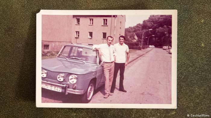 A photo of two men standing next to a car in a photo from the making of the film.