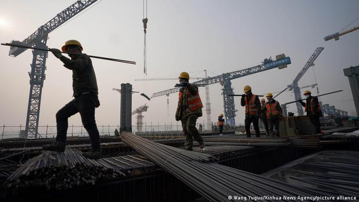 Workers work on a construction site at Fengtai Railway Station in Fengtai District of Beijing, capital of China