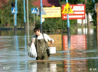 An unidentified citizen walks through the flooded area on the outskirts of the town of Jaslo
