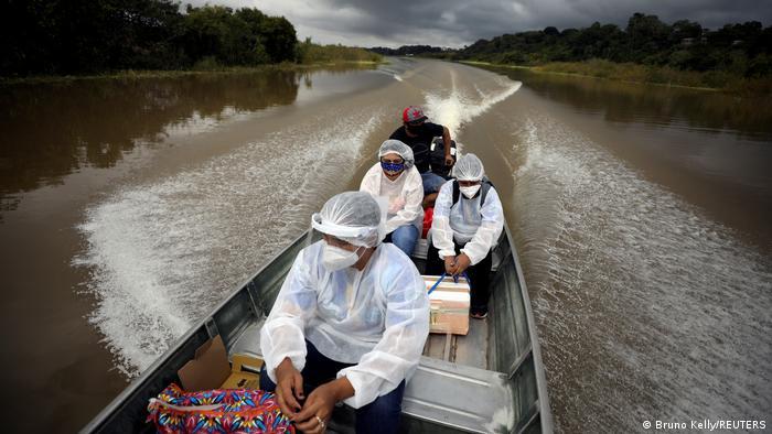 Três pessoas com roupa branca, touca e máscara estão em um pequeno barco que está em um rio. Há uma quarta pessoa, de preto, que parece controlar o motor.