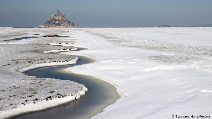 Este paisaje invernal de la costa normanda parece una pintura. La playa cubierta de espesa nieve, las olas del mar congeladas por el frío. Mont-Saint-Michel, una antigua abadía benedictina, se eleva sobre este paisaje casi irreal que la onda fría dejó para el recuerdo en el norte de Francia.