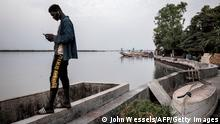 08.02.21 *** A man looks at his cellphone as he stands on the banks of the Casamance river in Ziguinchor on February 8, 2021. - The conflict in Casamance, which is separated from the rest of Senegal by The Gambia, has claimed thousands of lives since it first broke out in 1982. The army launched an operation on January 26, 2021 to secure the region and took hold of several bases from the MFDC rebels, including one of their main and historical bases in the Blaze Forest. (Photo by JOHN WESSELS / AFP) (Photo by JOHN WESSELS/AFP via Getty Images)