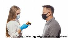 Looking at non-contact thermometer nurse testing employee's or patients body temperature wearing a medical face mask. Sad man wearing reusable face mask isolated on white background.