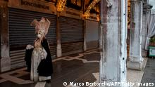 A Venetian artisan wearing a carnival mask and costume is pictured prior to take part in a demonstration of The Confederation of Venice Artisans (Confartigianato Venezia) at St. Mark's square in Venice on February 7, 2021, as the carnival is being cancelled due to the Covid-19 pandemic. - The trade association represents and protects more than 1,500 small businesses, not only craftsmen, in the Venice historical centre, the Islands and surrounding municipalities. (Photo by Marco Bertorello / AFP) (Photo by MARCO BERTORELLO/AFP via Getty Images)