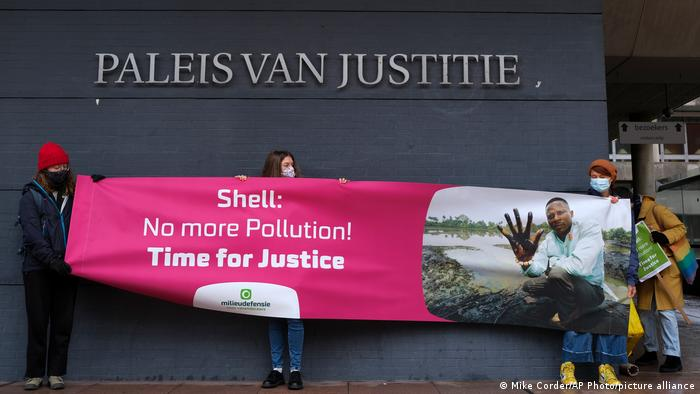 Friends of the Earth supporters hold a banner reading 'no more pollution outside the district court in The Hague, Netherlands
