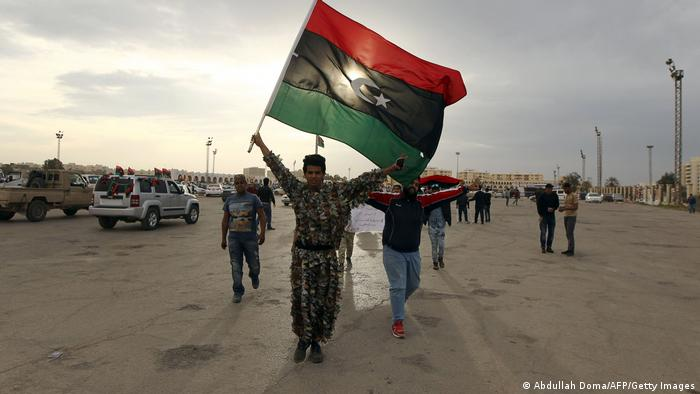 Libyan men in Benghazi wave their national flag during a demonstration marking the fifth anniversary of the Libyan revolution