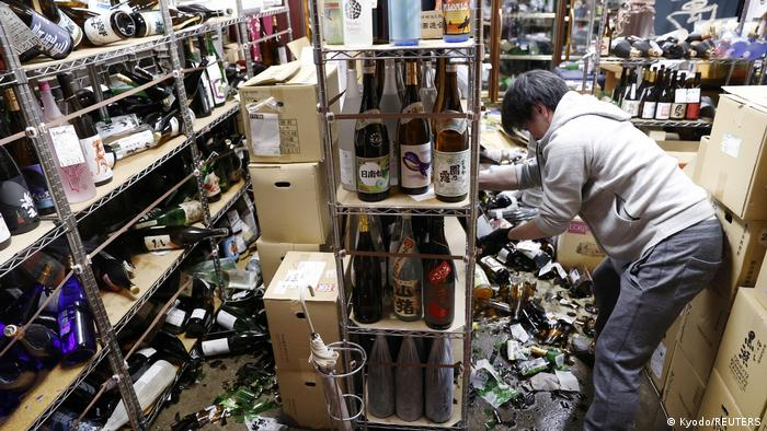 A worker cleans up broken bottles at a liquor shop after the earthquake in Fukushima, Japan.