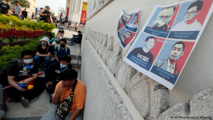 Protesters sitting on the ground as photos of the detained activists are hung on the wall in Bangkok.