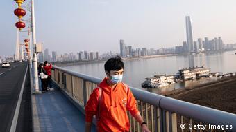 Мужчина в медицинской маске идет по мосту в китайском городе Ухань