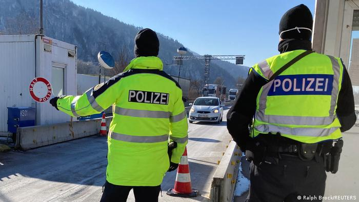 German border police wearing hi-visibility vests check vehicles arriving from Austria's Tyrol province
