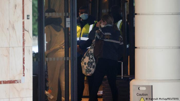 A security guard in a hi-vis vest opens the door to a woman arriving at a quarantine hotel