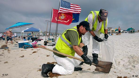 Workers hired by BP pick up tar balls as they work along Pensacola Beach, Florida