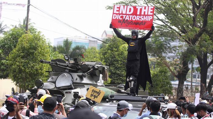 Ein als Batman verkleideter Demonstrant stellt sich auf einen Panzer in Yangon