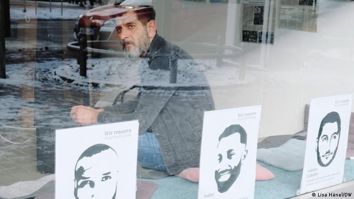 Cetin Gültekin sitting behind a window on which drawings of victims' faces can be seen