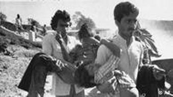 In this file photo, two men carry children blinded by the Union Carbide chemical pesticide leak to a hospital in Bhopal